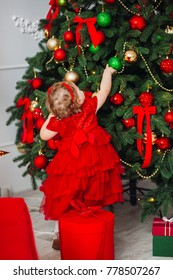 Pretty little girl in red dress looks funny posing in cosy room decorated for winter holidays