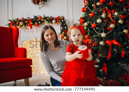b6e7e47b0d2ac Pretty little girl in red dress looks funny posing in cosy room decorated  for winter holidays