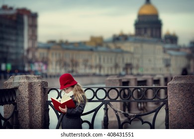 A pretty little girl with a red hat and coat reading a book on the streets of St. Petersburg, Moika river embankment, St. Isaac's Cathedral. Cloudy spring day.Children in the city. Beautiful city.