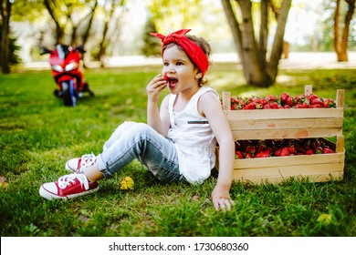 Pretty Little Girl in red Vintage 50s Style Pin Up Bow Head Scarf Bandana and white t-shirt eating strawberries on the summer grass