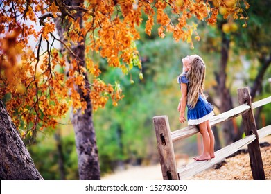 Pretty little girl relax on beauty autumn landscape background