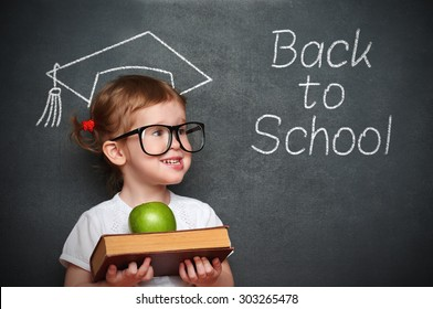 pretty little girl schoolgirl with books and apple in a school board