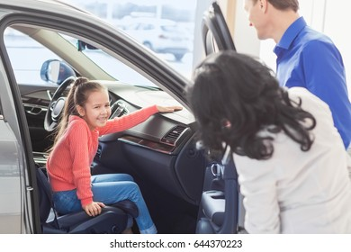 Pretty little girl sitting in a car laughing her parents standing near copyspace happy family choosing a new car at the dealership consumerism purchasing clients buyers sales transportation lifestyle