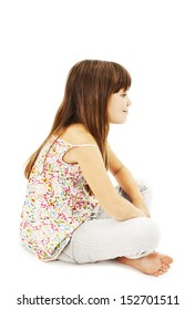 Pretty little girl sitting on the floor in jeans, profile. Isolated on white background