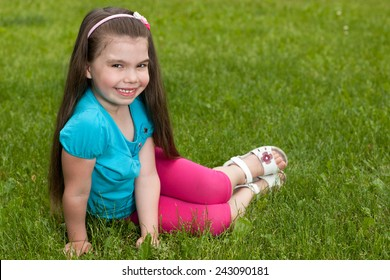 A pretty little girl is sitting on the green grass