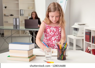Pretty little girl sketching at a table in a classroom or home office with a teacher or her mother sitting in the background working at a laptop and keeping an eye on her