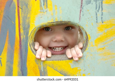 Pretty little girl smile and look out of the hole in painted wall.