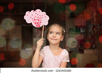 Pretty little girl in soft pink dress thinking about love and looking coquettish, she falls in love, romantic and love concept, Valentine Day greeting