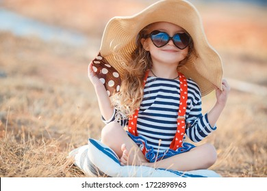 Pretty little girl in a striped dress and hat relaxing on the beach near sea, summer, vacation, travel concept. smiling cute little girl on beach vacation. Baby girl in hat and sun glasses on beach