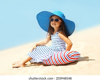 Pretty little girl in a striped dress and hat relaxing on the beach near sea, summer, vacation, travel - concept