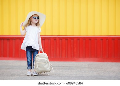 Pretty little girl in a striped dress and hat relaxing on the beach near sea, summer, vacation, travel concept. smiling cute little girl on beach vacation.