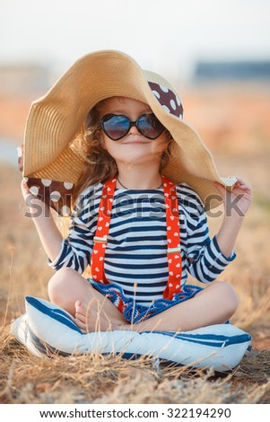 58f142f6a6a Pretty little girl in a striped dress and hat relaxing on the beach near  sea,