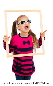 Pretty little girl in sunglasses looking through empty wooden frame, making funny face expression, isolated