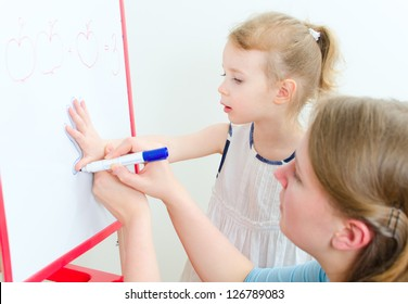 Pretty little girl with teacher near whiteboard