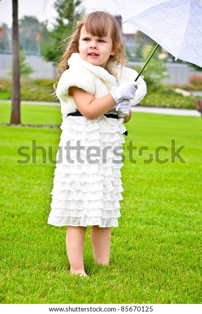 Pretty little girl with umbrella in the park barefooted