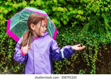 Pretty little girl under the rain, wearing purple rain coat, holding umbrella