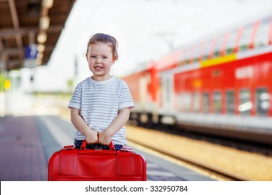 Pretty little girl walking with big red suitcase on a railway station. Kid waiting for train and happy about a journey. People, travel, lifestyle concept