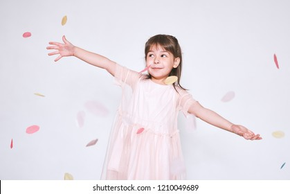 Pretty little girl wearing pink dress in tulle with princess crown on head isolated on white background rise hands enjoy confetti surprise. Cute smiling girl celebrating her birthday party having fun