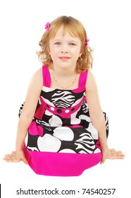 Pretty little girl wearing a pink  and black summer dress smiling sitting on the floor  isolated on white background.