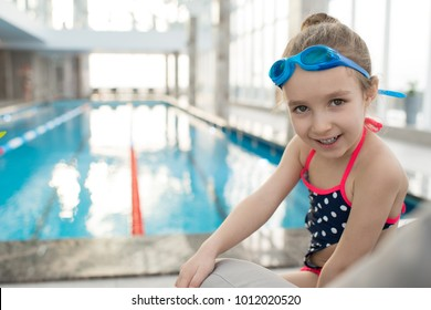 Pretty little girl wearing swimsuit and goggles sitting on deck chair and posing for photography while taking break from swimming in spacious pool, portrait shot