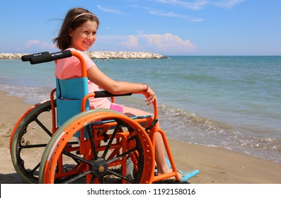 pretty little girl in the wheelchair by the sea in the summer