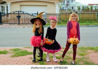 Pretty little girls with halloween treats celebrating traditional holiday
