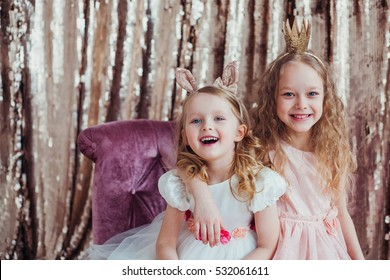 Pretty little girls posing against the golden background. Fashion photo. Christmas, birthday, party time.