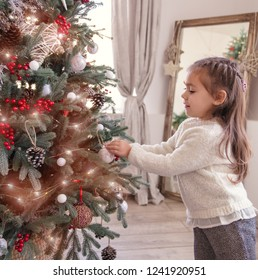 Pretty little happy girl decorating the Christmas tree. preparation for Christmas holiday.