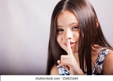 Pretty little Hispanic girl gesturing to keep it quiet or to keep a secret with her finger
