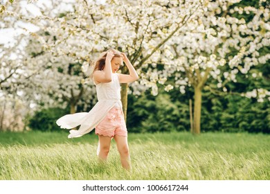 Pretty little kid girl playing in spring blooming garden