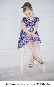 Pretty little lady sitting on a chair in a white room with classic interior. Kid's fashion.