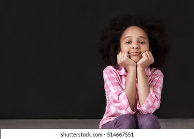 Pretty little mulatto girl sitting on the floor and holding hands on chin on black background