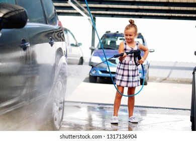 Pretty little preschool girl in summer dress helping to parents use coin-operated self-serve car wash, cleaning auto exterior holding high-pressure sprayer standing outdoors