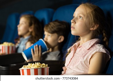 Pretty little red haired girl looking at the screen interestedly sitting at the cinema with her friends movies films premiere enjoyment recreation weekend lifestyle childhood children concept