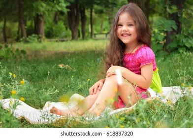 Pretty little sitting on a green grass