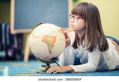 Pretty little student girl studying geography with globe in a child's room.