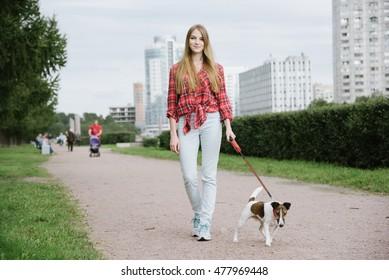 Pretty long hair girl walking her dog on a leash,