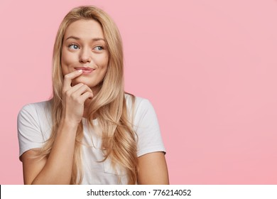 Pretty lovely blonde female with pure healthy skin dressed casually looks with dreamy expression aside, remembers pleasant moments, isolated over pink background, copy space for your advertisment