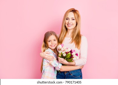 Pretty, lovely mom and daughter celebrating women's day, embracing over oink background, holding colorful tulips, looking at camera, leisure, happiness, fun, respect