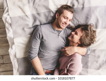 Pretty loving couple is luxuriating in bed together. They are hugging and smiling.