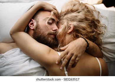 Pretty loving couple is luxuriating in bed together. They are hugging and smiling