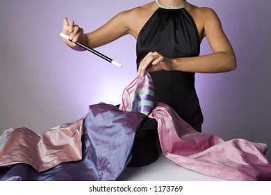 Pretty magician pulling fabric out of a hat