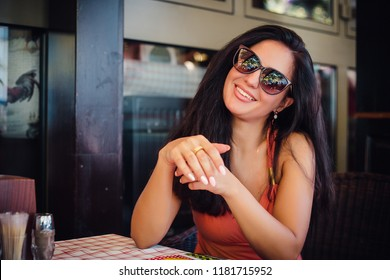 Pretty make up brunette girl is sitting at the restaurant, sexy girl in sunglasses outdoor posing, big lips, cleavage, laugh, attractive, long hair, brunette, happy model, skin care, tan, rings