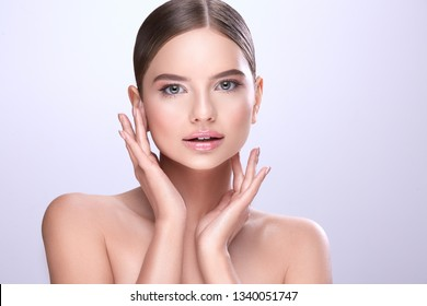 Pretty make up model with naked shoulders, fixed hair and nude make up posing at white background, make up tutorial, holding hand near face and looking at camera.