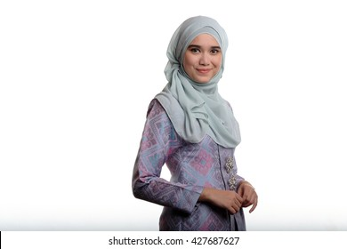 Pretty malay muslim lady wearing a traditional malay costume known as songket is smiling on white background
