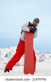 Pretty man with red snowboard in red pants