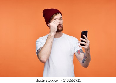 pretty man in white t-shirt hat on his head phone in hands orange pattern background