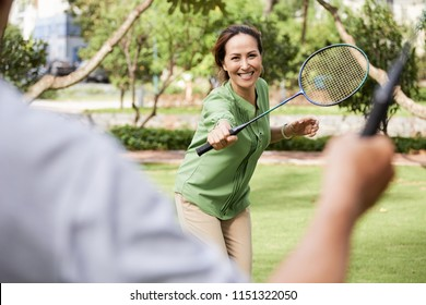 Pretty mature Asian woman playing badminton on summer day