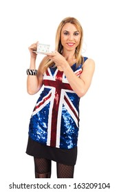 Pretty middle age woman wearing a sequin blouse with the British flag holding a cup of tea.