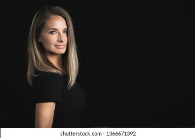 Pretty middle aged blonde woman on black background.